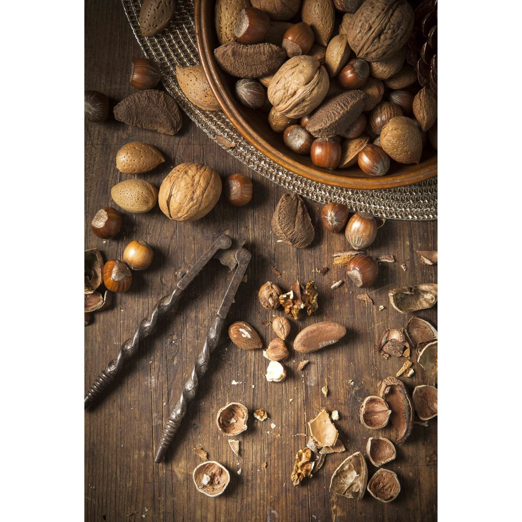 Festive bowl of mixed whole nuts in shells in a wooden bowl on a gold placemat with a vintage metal nutcracker surrounds by mixed nuts and broken nutshell on a rustic wooden table