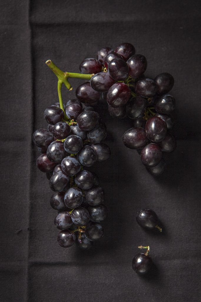Black grapes on black cloth by Stacy Grant